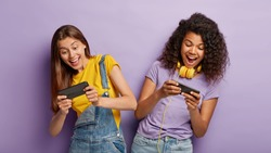Carefree outgoing teenage gamers play online games, win first place or gain highest score, tilt from each other, look with passion, being addicted gamblers, entertained with awesome application