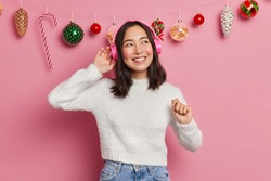 Carefree positive Asian girl wears stereo headphones and enjoys listening favorite music on New Years Eve dressed in casual white jumper poses against pink background with hanging christmas toys