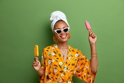 Carefree positive dark skinned woman holds delicious ice cream, popsicles on stick, has fun during summer time, wears stylish sunglasses, yellow robe, wrapped towel on head, has sweet tooth.