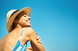 Carefree relaxed woman in hat enjoying summer beach vacation. Smiling tanned girl feeling hapiness and refreshed against bright blu sky