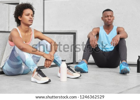 Carefree restful black sister and brother deep in thoughts, have break after jogging, wear casual comfortable clothes, surrounded with bottle filled with water to have energy. Youth and sport concept #1246362529