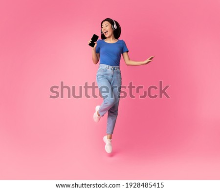 Carefree Singer. Asian lady singing favorite song and using cell phone as a mic, dancing and jumping, wearing wireless headphones. Excited woman having fun at pink studio, enjoying sound, full length