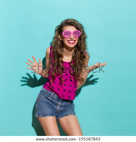 Carefree smiling girl. Beautiful woman in heart shaped glasses is smiling with arms outstretched. Three quarter length studio shot on teal background.