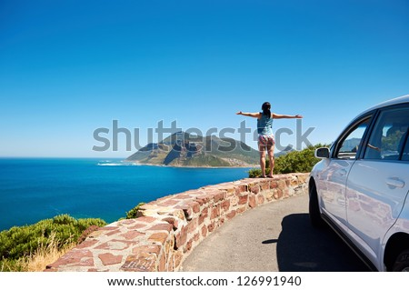 carefree tourist stands on chapmans peak drive with arms outstretched in freedom girl pose with rental car #126991940