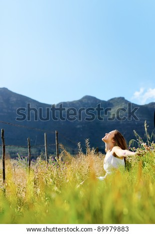 carefree vitality woman is happy outdoor in a field.  large panorama image with copyspace.