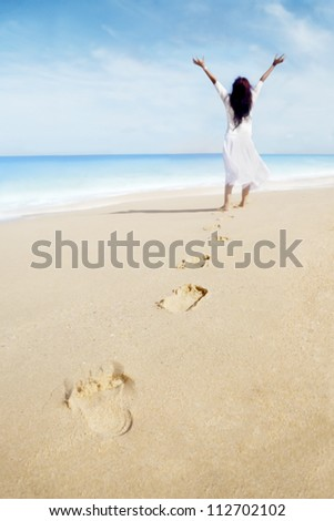 Carefree woman and footprints on the sand. shot at the tropical beach