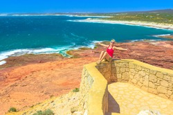Carefree woman at Red Bluff in Kalbarri National Park. Pederick Lookout overlooking Red Bluff Beach in Australian Coral Coast on Indian Ocean. Sunny with blue sky. Western Australia coastal lookout.