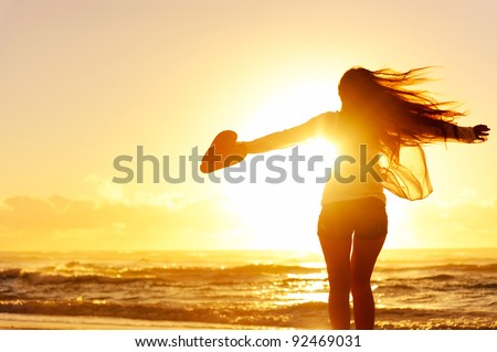 carefree woman dancing in the sunset on the beach. vacation vitality healthy living concept #92469031