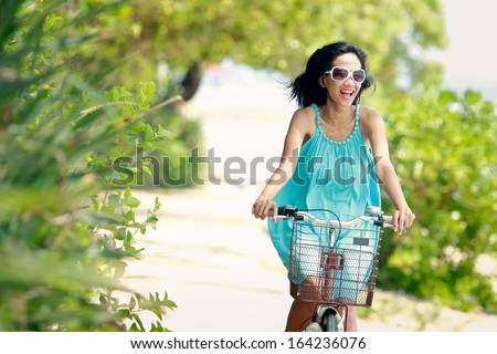 carefree woman having fun and smiling riding bicycle at the beach
