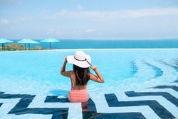 Carefree Woman in bikini and a straw hat relaxing in infinity swimming pool looking at  seaview. Luxury resort. Beautiful destination summer vacations. Back view