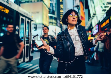 Carefree woman in eyewear with night city light reflection dancing on crowded street listening music via blank smartphone and earphones, youthful hipster girl enjoying favorite song on mockup mobile