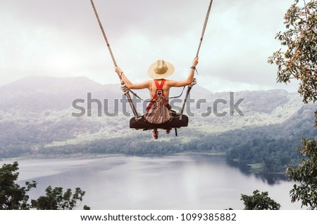Carefree woman on the swing on a inspiring landscape. Dream concept