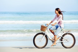 carefree woman with bicycle riding on beach sand having fun and smiling