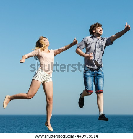 Carefree young couple friends jumping by sea ocean water. Happy woman and man having fun. Summer happiness and freedom. #440958514