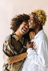 Carefree young gay couple standing together in a studio. Two affectionate male lovers smiling cheerfully while embracing each other against a studio background. Young gay coupe being romantic.