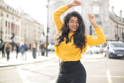 Carefree young indian woman in casual shirt and jeans dancing with joy with raised hands on city street