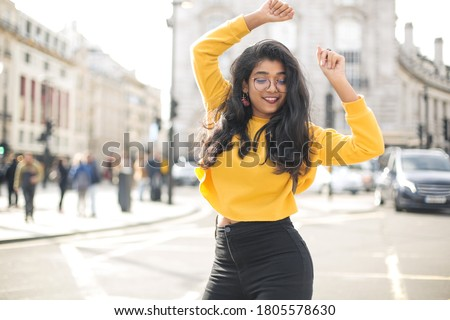 Carefree young indian woman in casual shirt and jeans dancing with joy with raised hands on city street Stockfoto ©
