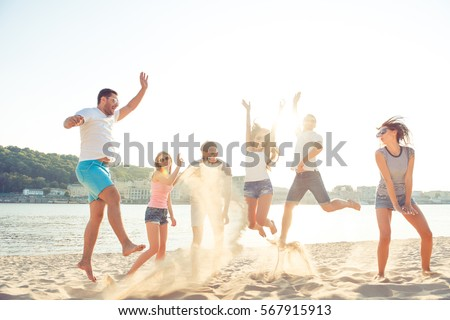 Carefree young people having fun and jumping on the seaside.