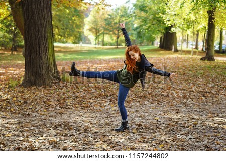 Carefree young redhead woman in a park kicking the fallen autumn leaves with outstretched arms and a happy smile #1157244802