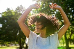 Carefree young woman dancing with her arms raised outside in a park on a sunny summer afternoon twirling her curly hair