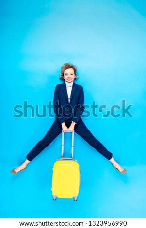 Carefree young woman holding yellow valise on blue background