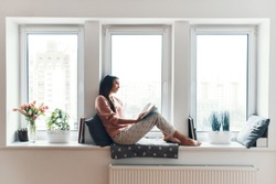 Carefree young woman in cozy pajamas reading a book while resting on the window sill at home