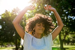 Carefree young woman twirling her curly hair while dancing with her arms raised outside in a park on a sunny summer afternoon