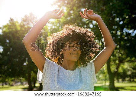 Carefree young woman twirling her curly hair while dancing with her arms raised outside in a park on a sunny summer afternoon Foto stock ©