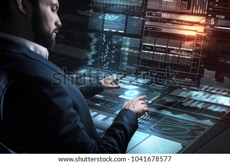 Careful specialist. Calm concentrated young programmer carefully touching a futuristic screen while working with modern transparent device in his office #1041678577