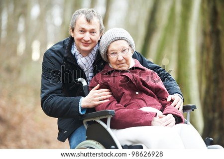 Caregiver careful man walking and embracing disabled senior elderly woman grandmother at wheelchair in nature