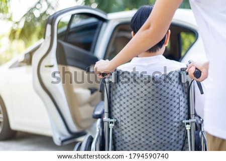 Caregiver helping senior handicapped asian woman from wheelchair get into car Photo stock ©