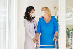 Caregiver in medical mask helping senior woman to move with help of walker