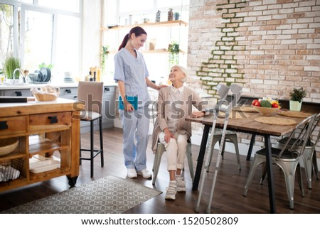 Caregiver in uniform. Caregiver in uniform coming to visit aged woman having knee ache