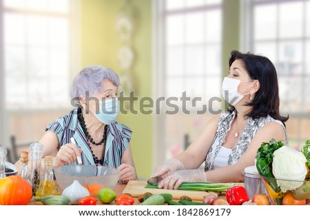 Caregiver or companion and senior adult woman speak in a friendly manner as they cook a vegetable salad together. Both are wearing protective face masks due to the coronavirus pandemic now.