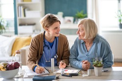 Caregiver or healthcare worker with senior woman patient, explaining how to use litmus paper.