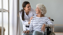 Caregiver supporting happy disabled older woman sitting in wheelchair close up, touching shoulders, expressing care and love, smiling nurse wearing white uniform and mature patient having fun