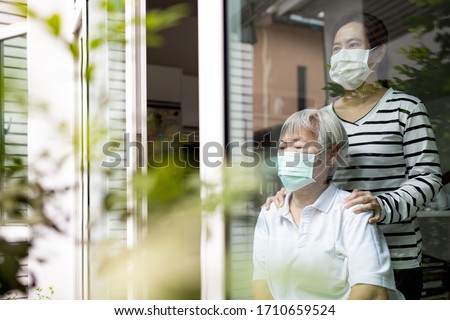Caregiver woman is taking care of senior,sad elderly is looking outside through window feeling bored,depressed,stressed,life depression of old people,stay home during Covid-19,Coronavirus pandemic