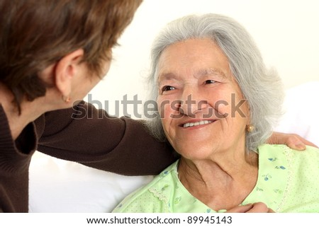 Careing for a elderly woman lying in bed