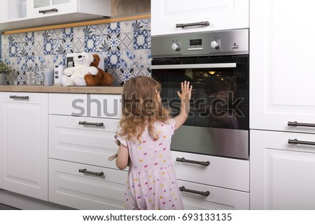 careless naive child girl touches hot glass door of oven in the kitchen #693133135