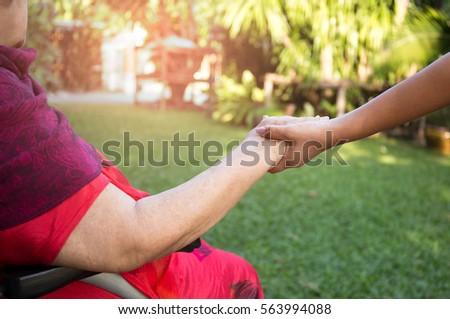 Caretaker pushing senior woman in wheel chair out for fresh air #563994088