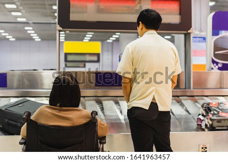 Caretaker with senior woman in wheelchair wiat for luggage on conveyor belt in the airport. Zdjęcia stock ©