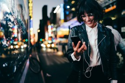 Carfree millennial influencer in earphones watching online video streams on modern cellphone technology enjoying web browsing in night city, joyful hipster girl in eyewear installing media app