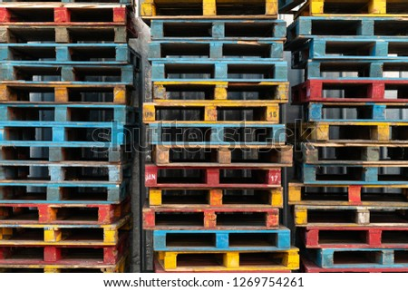 cargo and shipping concept : Stacked of colorful rough wooden pallets background at warehouse.