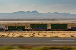 Cargo container freight train in motion speed blur through the desert landscape railway. Logistics