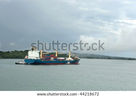 Cargo container ship in canal being escorted by tug boats.