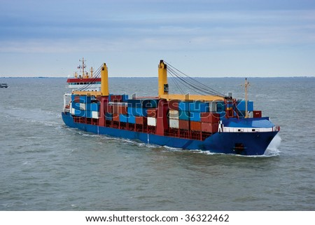 Cargo container ship loaded in channel headed out to sea.