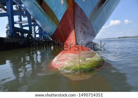 Cargo container ship moored in the port, view on the ships bulbous bow.