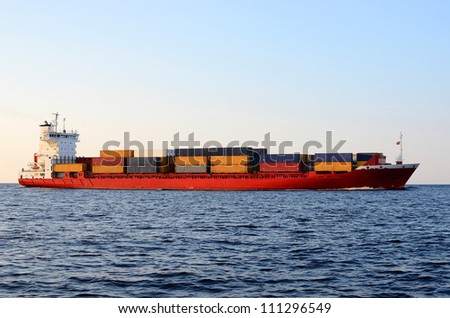 cargo container ship sailing at the sunset
