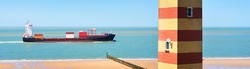 Cargo container ship sailing in the sea. Coast of Vlissingen, the Netherlands. Dunes and a striped lighthouse. Freight transportation, nautical vessel, logistics, industry, environment. Panoramic view