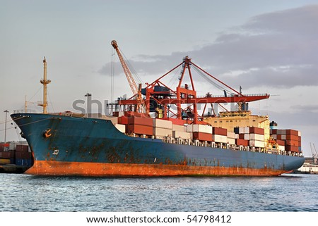 Cargo container ship under cranes in the sea port
